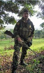 MILITÆRT UTSTYR: Tjostolv Moland iført militæruniform på en skytebane i Uganda. I hånden holder han en rifle med kikkertsikte. (Foto: Privat)