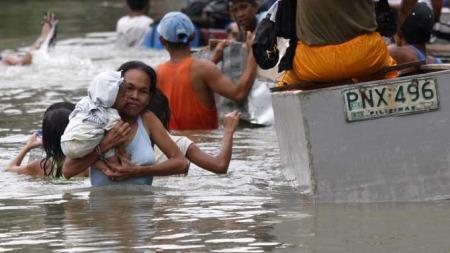 En filippinsk mor med barnet på armen, vasser gjennom flomvannet etter tyfonen Ketsana.  (Foto: EPA/Dennis M. Sabangen)