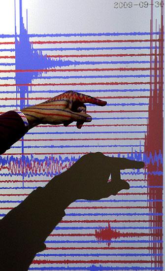 HER ER SKJELVET: Den tyske seismologen Winfried Hanka viser hvordan seismografen gjorde utslag da jordskjelvet inntraff i Stillehavet, utenfor Samoas kyst. Resultatet ble en tsunami som drepte over 100 mennesker og skadet mange flere. (Foto: REUTERS/Fabrizio Bensch )