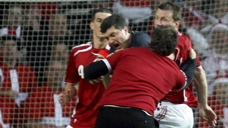 HER GÅR DET GALT: Den berusede dansken går til angrep på dommer Herbert Fandel. (Foto: LISELOTTE SABROE/AFP)