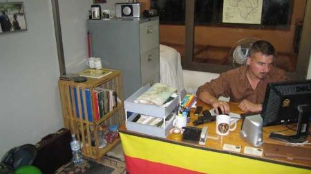 PÅ KONTORET: Her sitter Tjostolv Moland på kontoret som han delte med Joshua French i Ugandas hovedstad Kampala. På bordet ligger en pistol av merket P-80 Glock. (Foto: Privat)