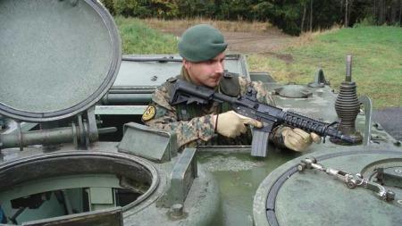 PANSERVOGN: Her poserer Tjostolv Moland iført SIG-merket uniform, dødningehodeberet og våpen om bord i en M113 personellpanservogn. Det er ikke kjent om våpenet er ekte. (Foto: Privat)