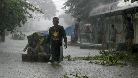 Ikke alle har flyktet fra uværet. I Angono forsøker folk å fortsette hverdagen i flomvannet. (Foto: BULLIT MARQUEZ/AP)