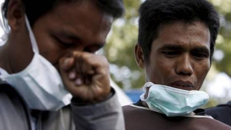 Slekninger til en av gjestene på Ambacang Hotel gråter etter å ha hørt nyhetene om katastrofen. (Foto: NICKY LOH/REUTERS)