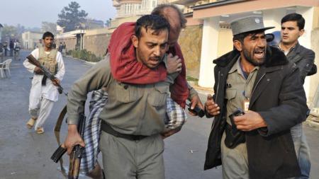DRAMATISK: En mann reddes av en afghansk politimann etter at han ble skadet i terrorangrepet i Kabul onsdag 28.oktober. (Foto: AFP/SCANPIX)