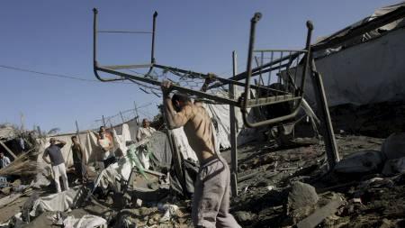 RUINER: Palestinere i ruinene etter et israelsk luftangrep på det som skal ha vært en palestinsk våpenfabrikk. (Foto: EYAD BABA/AP)