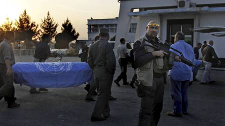 HØSTEN 2009: Sikkerhetsvakter passer på mens kistene til FN-arbeiderne som ble drept i angrepet i Kabul bæres ut. (Foto: Gemunu Amarasinghe/AP)