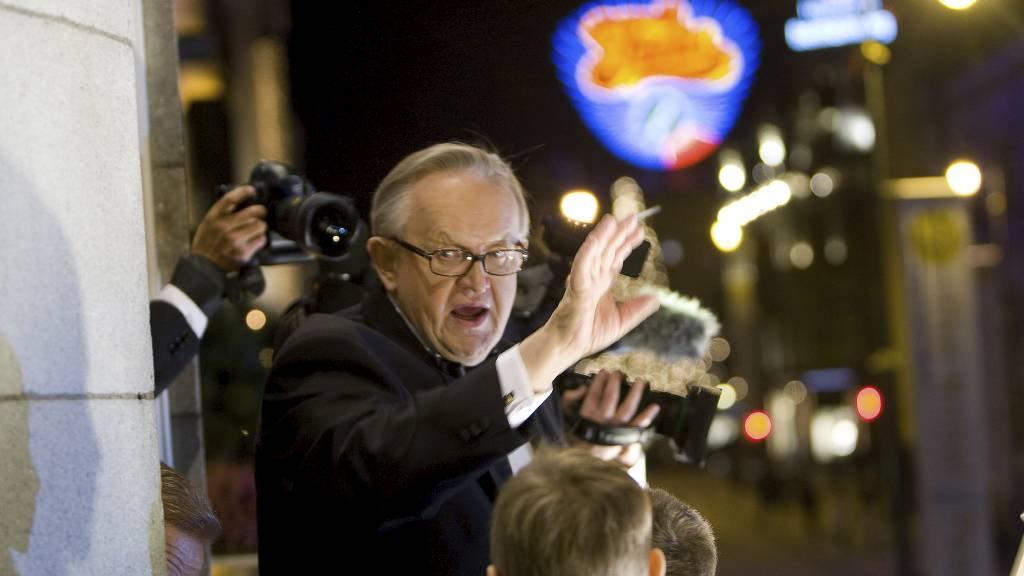 Fjorårets vinner av Nobels fredspris, finske Martti Ahtisaari, hilser fakkeltoget til hans ære fra balkongen på Grand Hotel. (Foto: Junge, Heiko/SCANPIX)