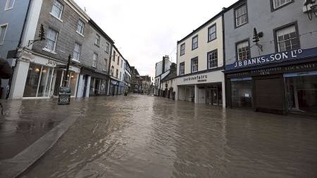 Vannet fyller gatene i landsbyen Cockermouth. Rundt 1000 hjem står i fare for å bli rammet av flommen. (Foto: ANDREW YATES/AFP)