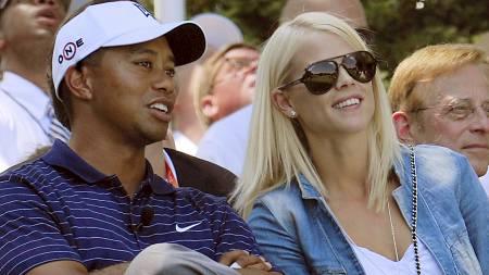 Tiger Woods of the US spekas with his wife Elin Nordegren (Foto: KAREN BLEIER/AFP)