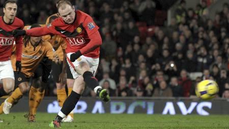 STRAFFET WOLVES: Wayne Rooney setter United i føringen fra krittmerket.   (Foto: PAUL ELLIS/AFP)