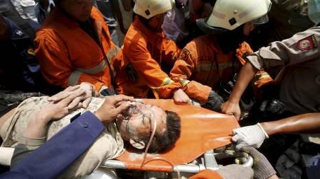 En overlevende blir fraktet ut av ruinene. To skal ha blitt   drept i kollapsen. (Foto: Tatan Syuflana/AP)