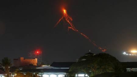 Vulkanen Mayon avbildet søndag. Glødende lava renner ned fjellsiden. (Foto: ERIK DE CASTRO/REUTERS)