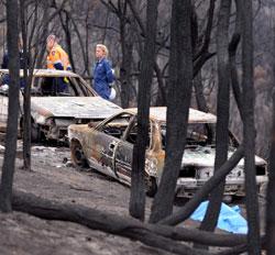 Politiet og rettsmedisinere undersøker ofre etter skogbrannen ved Kingslake 11. februar 2009.  (Foto: EPA)