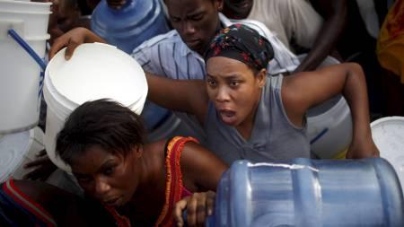 DESPERAT: En kvinne forsøker desperat å få rent vann ved en vannstasjon i Port-au-Prince (Foto: CARLOS BARRIA/REUTERS)