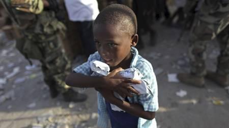 MAT: En gutt har fått tak i proteinkjeks fra en nødhjelpsstasjon i Port-au-Prince. (Foto: Ariana Cubillos/AP)