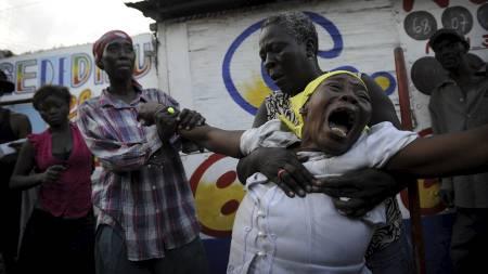 FORTVILER: Armante Cherisma gråter over datteren (15) som ble   skutt og drept av en politimann i Haiit. (Foto: Olivier Laban mattei/AFP)