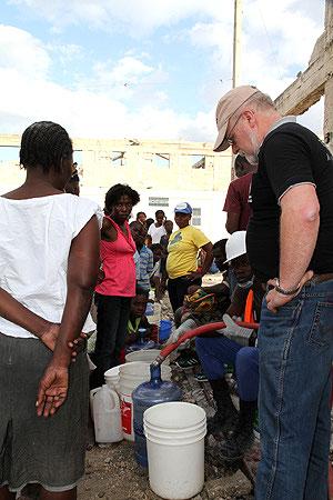 VANN TIL FOLKET: Her er Kirkens Nødhjelps generalsekretær med mens organisasjonen deler ut vann i en fattig bydel i Port-au-Prince. (Foto: Arne Grieg Riisnæs/Kirkens Nødhjelp)