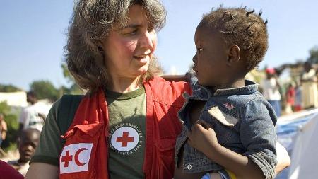 Winnie Romeril fra USAs Røde Kors bører lille Estphane Shan til en førstehjelpspost i bydelen Croix Desprez i Port-au-Prince. FN sa 19. januar at de mener det fortsatt er mulig å finne overlevende i ruinenene etter jordskjelvet som rammet Haiti 12. januar. (Foto: AFP PHOTO / AMERICAN RED CROSS)