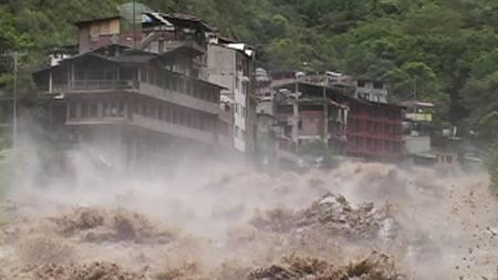 FLOM: Vannet flommer forbi bygniner i Machu Picchu Pueblo i Cuzco, Peru. (Foto: STRINGER/PERU/REUTERS)