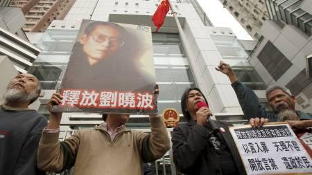Demokratiforkjempere holder plakater med bilder av den fengslede dissidenten Liu Xiaobo under en protest i Hong Kong 25 januar. (Foto: TYRONE SIU/REUTERS)