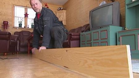 SIGER NED: Per Olav Flaker viser det skjeve gulvet i stua.
