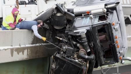 SIKRET: Redningsarbeidere førsøker å sikre trekkvognen  så den ikke faller utfor broen. (Foto: Chris Bergin/AP)