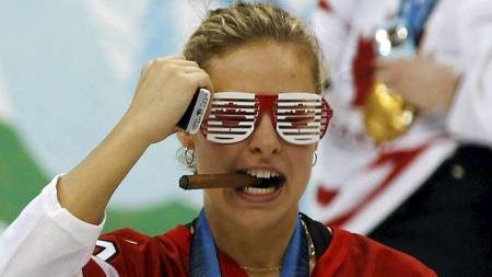 Canada's Tessa Bonhomme poses with a cigar and her gold medal during celebrations after their women's ice hockey gold medal game against the U.S (Foto: SCOTT AUDETTE/REUTERS)