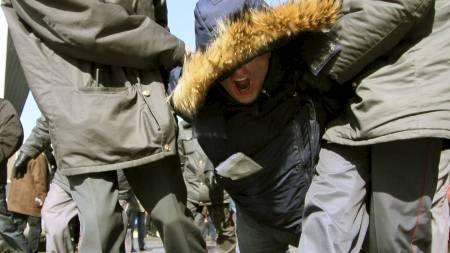 ARRESTERT:  En demonstrant blir anholdt i byen Irkutsk lørdag. I Moskva ble 70 opposisjonelle arrestert, ifølge politiet. (Foto: STRINGER/RUSSIA/REUTERS)
