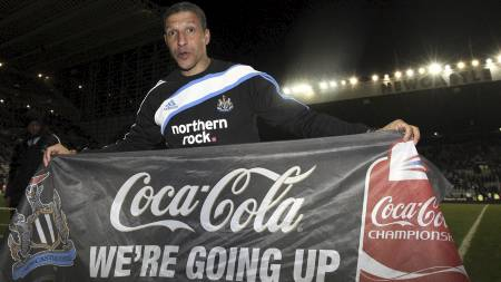Manager Chris Hughton holder opp et banner etter Newcastles opprykk til Premier League (Foto: SCOTT HEPPELL/AP)