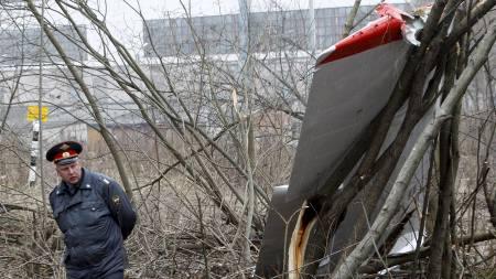 PRESIDENTENS FLY: En offiser for innenriksdepartementet står vakt foran en del av vraket av det polske flyet Tupolev Tu-154 som styrtet lørdag. (Foto: SERGEI KARPUKHIN/REUTERS)