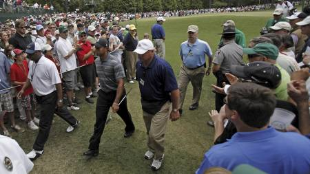 Escorted by security personnel, Tiger Woods walks to the second tee during the first round of the (Foto: Rob Carr/AP)