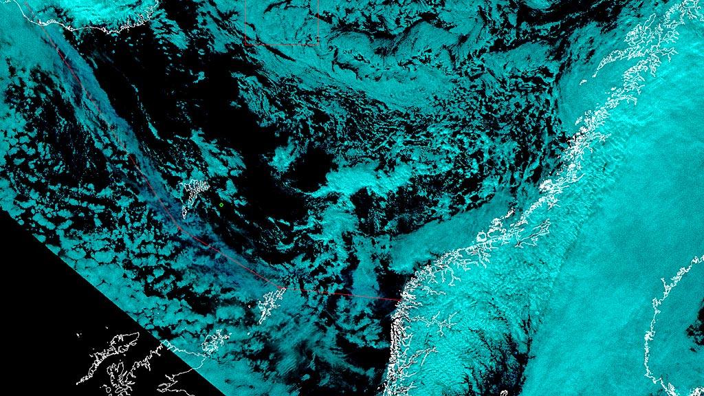 Øverst til venstre i bildet ser vi Island, og den blå skyen som  brer seg i sørøstlig retning er askeskyen, som føres mot Norge av vinden  - og er markert med en tynn, rød linje som viser lengdemålet på skyen.  (Foto: Bildet er tatt ned og prosessert av Kongsberg Satellite Services)