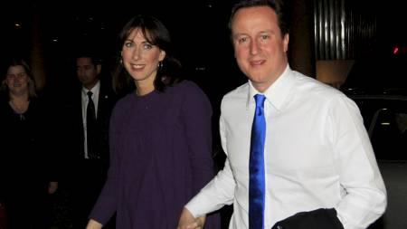 TROLIG VALGVINNER: Partileder David Cameron i De konservative sammen med sin kone Samantha ankommer partiets kontor i London tidlig fredag morgen. (Foto: Lefteris Pitarakis/Ap/Scanpix)