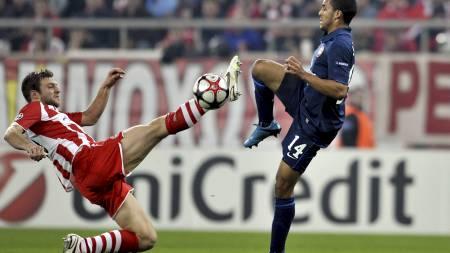 KNALLHARD: Hellas' Avraam Papadopoulos treffer kneet på motstanderen. (Foto: ARIS MESSINIS/AFP)