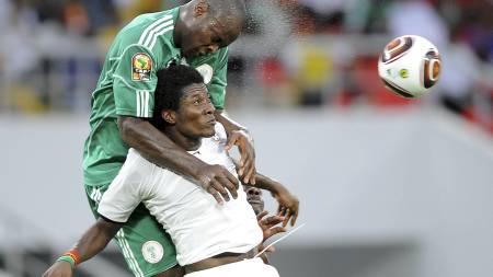 KLATRER: Nigerias Danny Shittu klatrer på  motstanderen. (Foto: JOE KLAMAR/AFP)