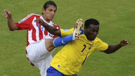 IKKE ETTER BALLEN: Paraguays Enrique Vera (til venste) går ikke etter ballen i duell med Ecuadors  Joffre Guerron. (Foto: RODRIGO BUENDIA/AFP)