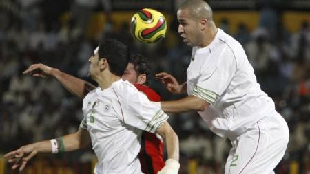 DYTT I RYGGEN: Algerias Majid Bougherra vinner en hodeduell med ulovlige midler. (Foto: Nasser Nasser/AP)