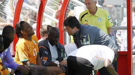 FÅR BEHANDLING: En bekymret Sven-Göran Eriksson (til høyre)   ser på at Didier Drogba mottar behandling. (Foto: Jean-Christophe Bott/Ap)