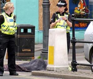 To politikvinner står ved siden av en av ofrene for skytingen i Whitehaven i Nordvest-England. (Foto: Scanpix)