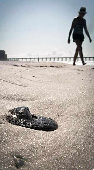 OLJE FRA DEEPWATER HORIZON: En turgåer passerer en oljeball på Pensacola Beach i Florida.