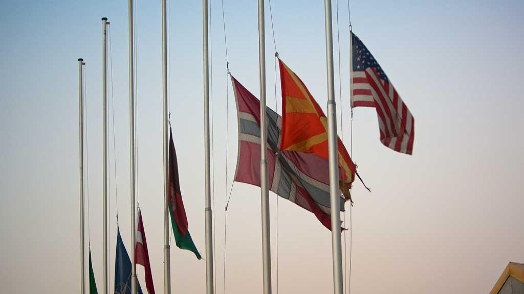 PÅ HALV STANG: Flaggene er senket på halv stang ved den norske leiren i Maimana i Afghanistan etter at fire norske soldater ble drept av en veibombe søndag. (Foto: Stephen Olsen/Forsvaret)