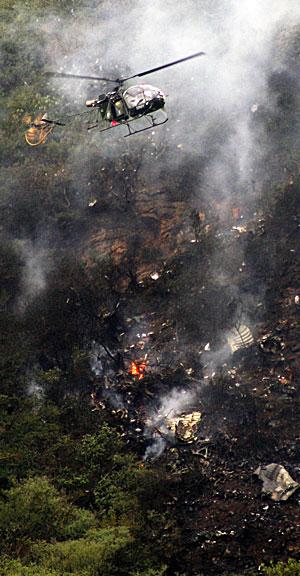 REDNINGSAKSJON: Et helikoter flyr over ulykkesstedet op let etter overlevende. (Foto:  REUTERS/Stringer )