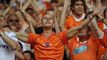 Blackpool supporters celebrate their first goal during the English Premier League football match between Wigan Athletic and Blackpool at The DW (Foto: PAUL ELLIS/Afp)