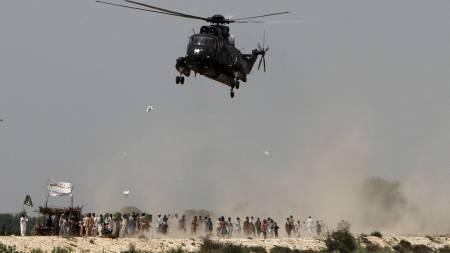NØDHJELP: Flomrammede samler seg under et militærhelikopter som akkurat har sluppet ut nødhjelpspakker i Khairpur. (Foto: Shakil Adil/Ap)