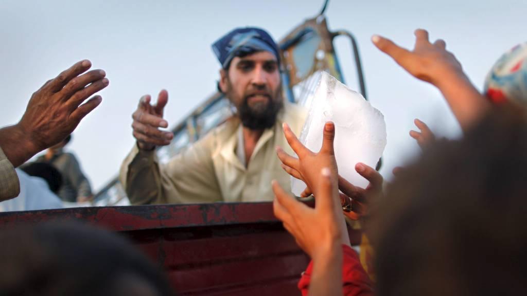 NØDHJELP: Barn griper etter hjelpesendingene som deles ut i nærheten av Peshawar i Pakistan. (Foto: TIM WIMBORNE/Reuters)