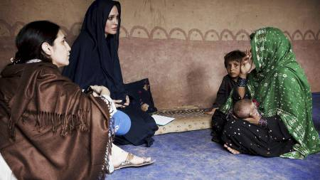 FRA HOLLYWOOD TIL FLOMOFRE: Angelina Jolie snakker med en familie som mistet hjemmet sitt etter flommen i Pakistan. (Foto: JASON TANNER/Afp)