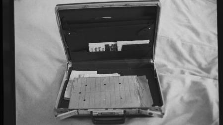 Dette bildet skal være tatt i Treholts leilighet i august 1983. Der finnes det taperester, men tapen synes ikke på kofferten som Treholt ble fotografert med på Fornebu i januar 1984. I forbindelse med rettssaken var tapen der igjen.