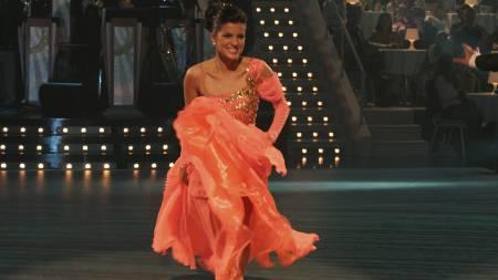 - Aylar bærer en korallfarget,   asymmetrisk kjole i gull. Som mange av kjolene i konkurransen er den   pyntet med Swarovski-krystaller, og da blir det veldig eksklusivt. Hun   har en skulder bar, og det kler henne. Fargen på kjolen passer perfekt   til hennes hudtoner og hårfarge, mener Lein. (Foto: Eirik Bratthammar/)