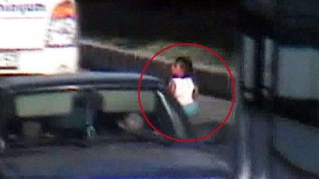 FRYKTLØS: Ettåringen satt midt på motorveien mens store lastebiler dundret forbi. (Foto: AP)